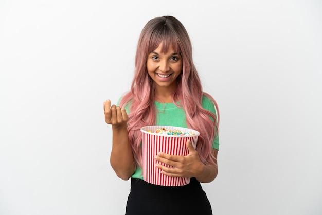 お金のジェスチャーを作る白い背景で隔離のポップコーンを食べるピンクの髪を持つ若い混血の女性