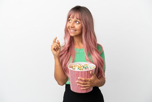 Молодая женщина смешанной расы с розовыми волосами ест попкорн на белом фоне, указывая на отличную идею