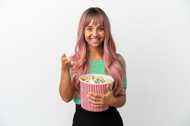 Молодая женщина смешанной расы с розовыми волосами ест попкорн на белом фоне, пожимая руку для заключения хорошей сделки