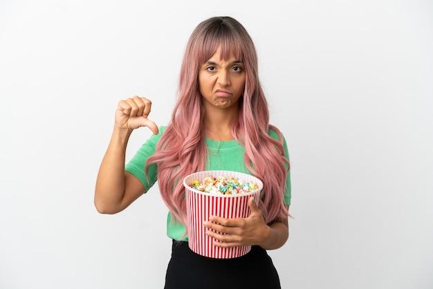 否定的な表現で親指を示す白い背景で隔離のポップコーンを食べるピンクの髪を持つ若い混血の女性