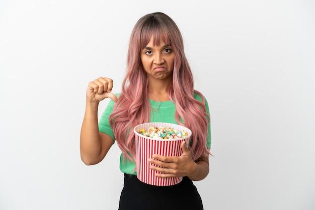 Молодая женщина смешанной расы с розовыми волосами ест попкорн на белом фоне, показывая большой палец вниз с отрицательным выражением лица