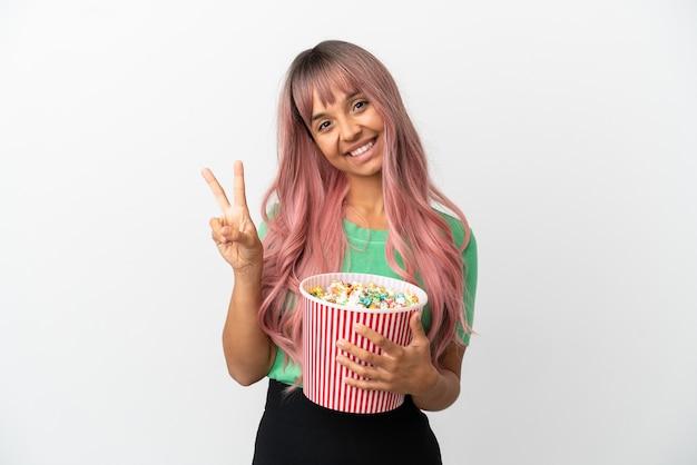 Молодая женщина смешанной расы с розовыми волосами ест попкорн на белом фоне улыбается и показывает знак победы