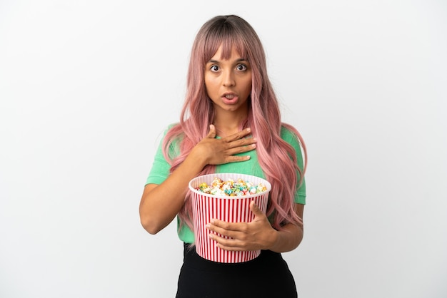 Молодая женщина смешанной расы с розовыми волосами ест попкорн на белом фоне удивлена и шокирована, глядя вправо