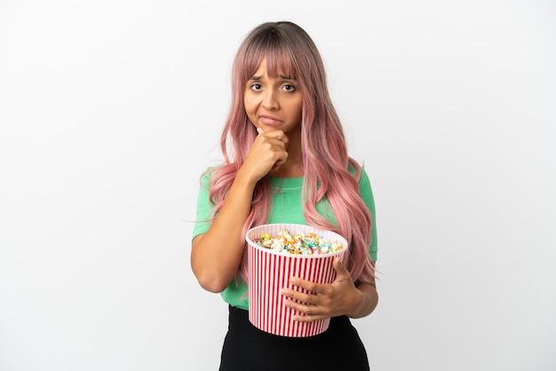白い背景思考で分離されたポップコーンを食べるピンクの髪を持つ若い混血の女性