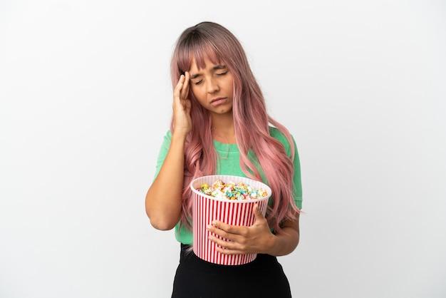 Молодая женщина смешанной расы с розовыми волосами ест попкорн на белом фоне с головной болью