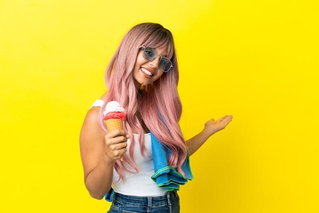 Молодая женщина смешанной расы с розовыми волосами держит мороженое на желтом фоне, протягивая руки в сторону, чтобы пригласить приехать