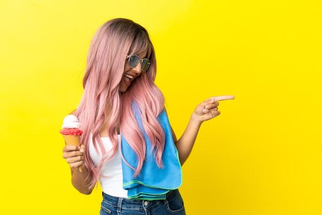 Молодая женщина смешанной расы с розовыми волосами держит мороженое на желтом фоне, указывая пальцем в сторону и представляет продукт