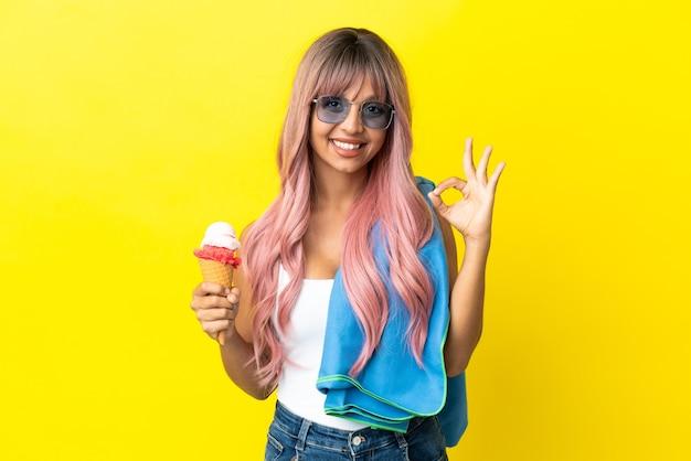 Молодая женщина смешанной расы с розовыми волосами держит мороженое на желтом фоне, показывая пальцами знак ок