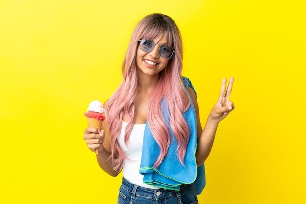Молодая женщина смешанной расы с розовыми волосами держит мороженое, изолированное на желтом фоне, улыбается и показывает знак победы