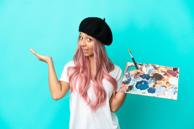 Young mixed race woman with pink hair holding a palette isolated on blue background extending hands to the side for inviting to come