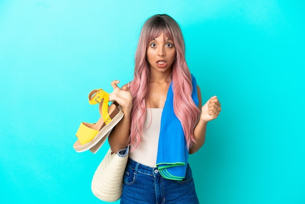 Young mixed race woman with pink hair holding summer sandals isolated on blue background celebrating a victory in winner position