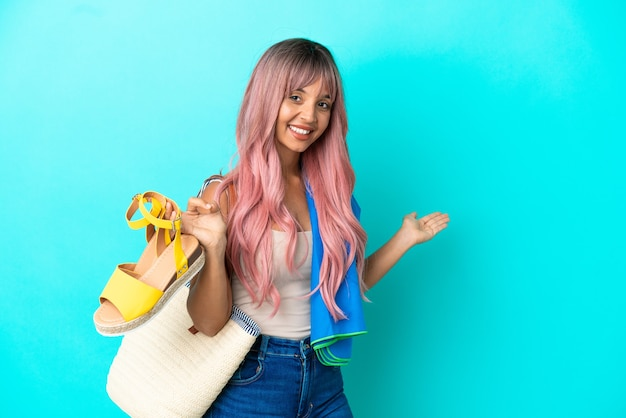 Young mixed race woman with pink hair holding summer sandals isolated on blue background extending hands to the side for inviting to come