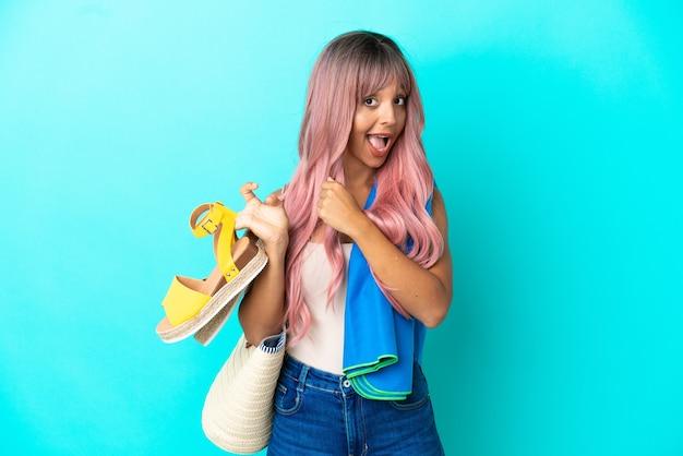 Молодая женщина смешанной расы с розовыми волосами, держащая летние сандалии на синем фоне, празднует победу