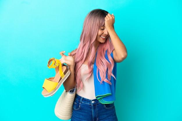 青い背景で隔離の夏のサンダルを保持しているピンクの髪を持つ若い混血の女性は何かを実現し、解決策を意図しています