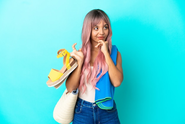 疑いを持って青い背景で隔離の夏のサンダルを保持しているピンクの髪を持つ若い混血の女性