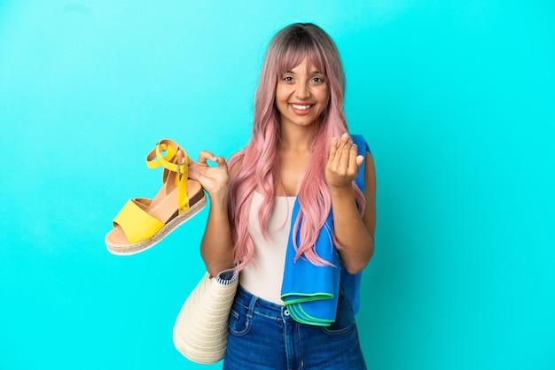 手で来るように誘う青い背景に分離された夏のサンダルを保持しているピンクの髪を持つ若い混血の女性。あなたが来て幸せ