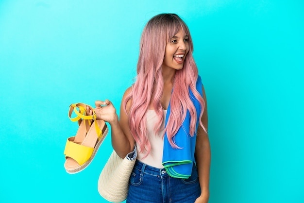 横の位置で笑って青い背景に分離された夏のサンダルを保持しているピンクの髪を持つ若い混血の女性