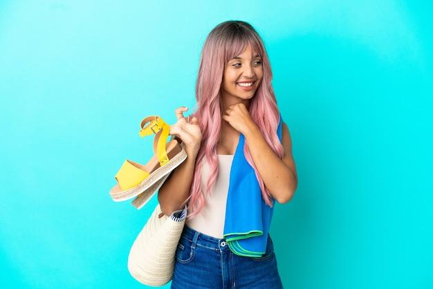 笑顔で見上げる青い背景に分離された夏のサンダルを保持しているピンクの髪を持つ若い混血の女性