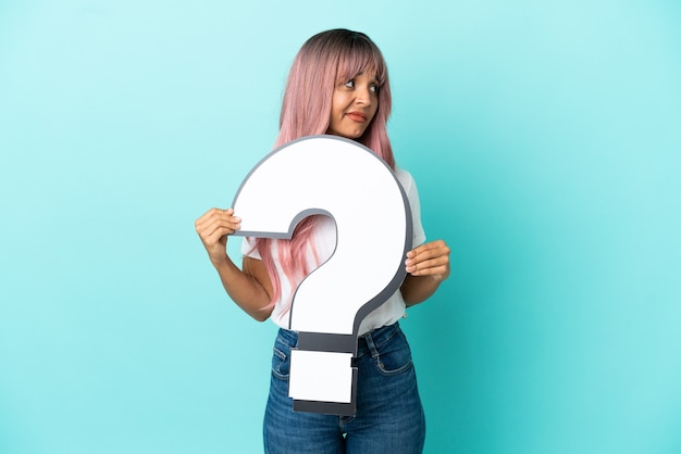 Young mixed race woman with pink hair isolated on blue background holding a question mark icon and looking side