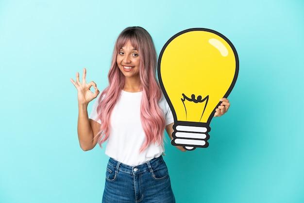 電球のアイコンを保持し、okサインをしている青い背景に分離されたピンクの髪を持つ若い混血の女性