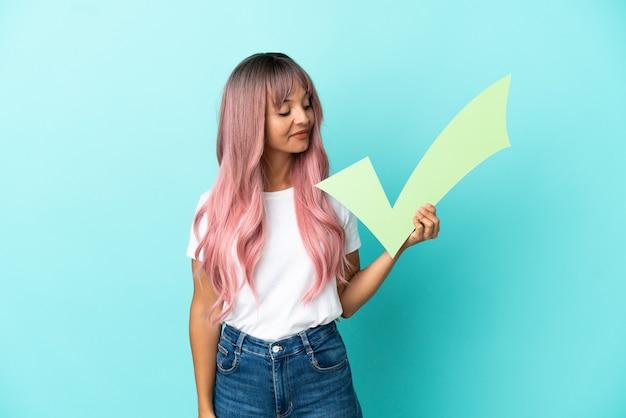 幸せな表情でチェックアイコンを保持している青い背景に分離されたピンクの髪を持つ若い混血の女性