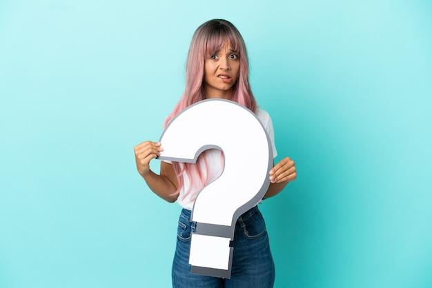 疑問符のアイコンを保持し、悲しい表情で青い背景に分離されたピンクの髪を持つ若い混血の女性