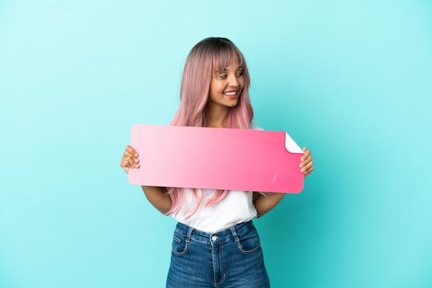 空のプラカードを保持し、側面を見て青い背景に分離されたピンクの髪を持つ若い混血の女性
