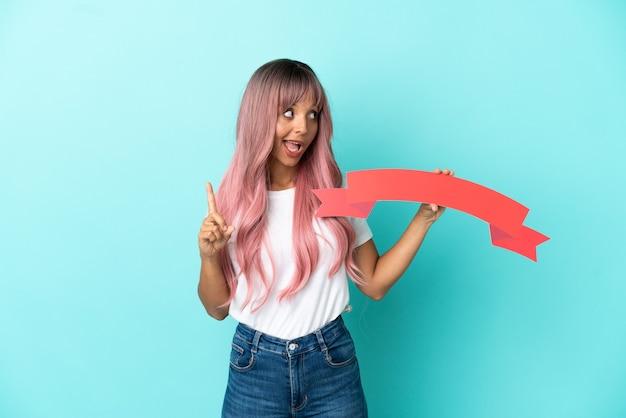 空のプラカードを保持し、考えている青い背景に分離されたピンクの髪を持つ若い混血の女性