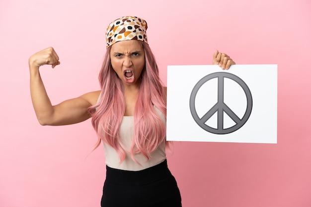 Молодая женщина смешанной расы с розовыми волосами, изолированная на розовом фоне, держит плакат с символом мира и делает сильный жест