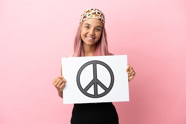 Молодая женщина смешанной расы с розовыми волосами, изолированная на розовом фоне, держит плакат с символом мира со счастливым выражением лица