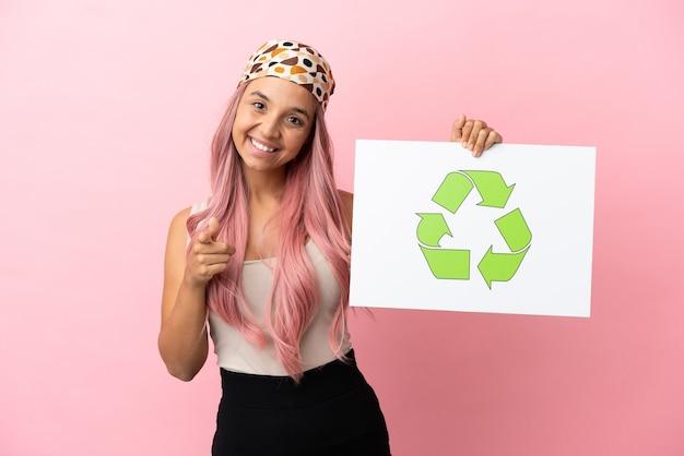 リサイクルアイコンと正面を指しているプラカードを保持しているピンクの背景に分離されたピンクの髪を持つ若い混血の女性
