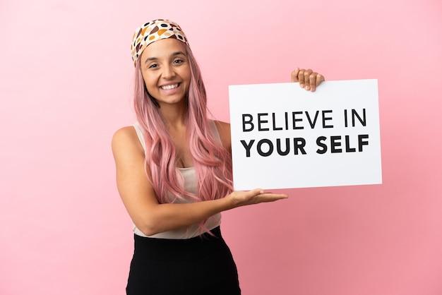분홍색 배경에 격리된 분홍색 머리를 한 젊은 혼혈 여성은 자신을 믿으라는 문구가 적힌 플래카드를 들고 그것을 가리키는