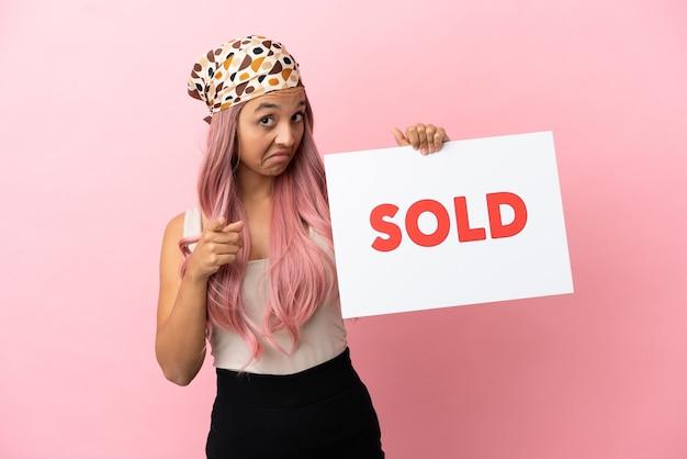 분홍색 배경에 격리된 분홍색 머리를 가진 젊은 혼혈 여성은 sold라는 문구가 적힌 플래카드를 들고 앞을 가리킵니다