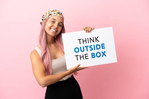 분홍색 배경에 격리된 분홍색 머리를 가진 젊은 혼혈 여성은 행복한 표정으로 상자 밖에서 생각하는 현수막을 들고
