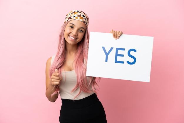 분홍색 배경에 격리된 분홍색 머리를 가진 젊은 혼혈 여성은 yes라는 문구가 적힌 플래카드를 들고 그것을 가리키는
