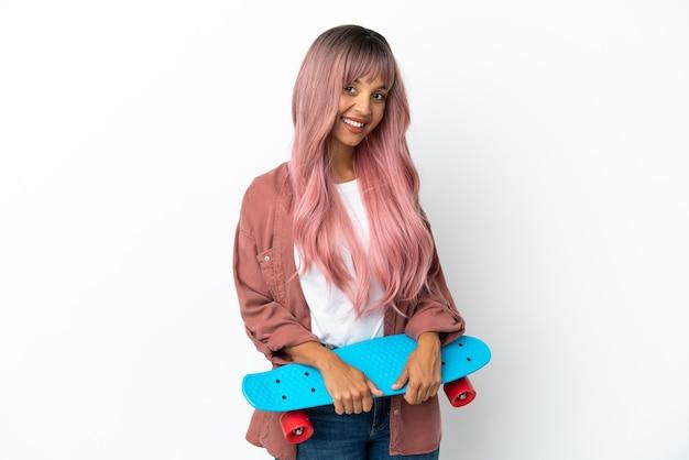 Молодая женщина смешанной расы с розовыми волосами изолирована на белом фоне с катанием на коньках со счастливым выражением лица