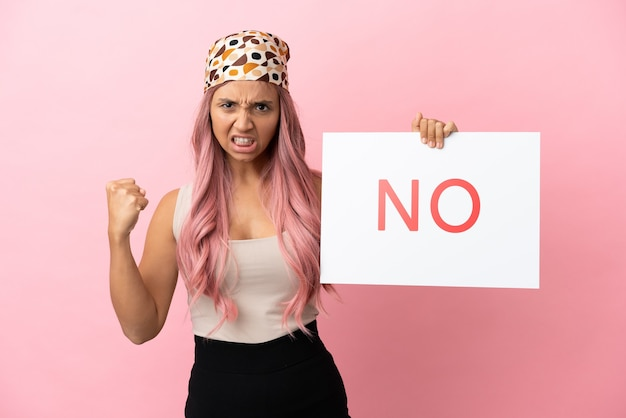 Young mixed race woman with pink hair isolated on pink background holding a placard with text no and angry