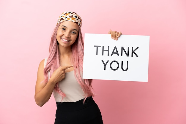 Young mixed race woman with pink hair isolated on pink background holding a placard with text thank you and  pointing it