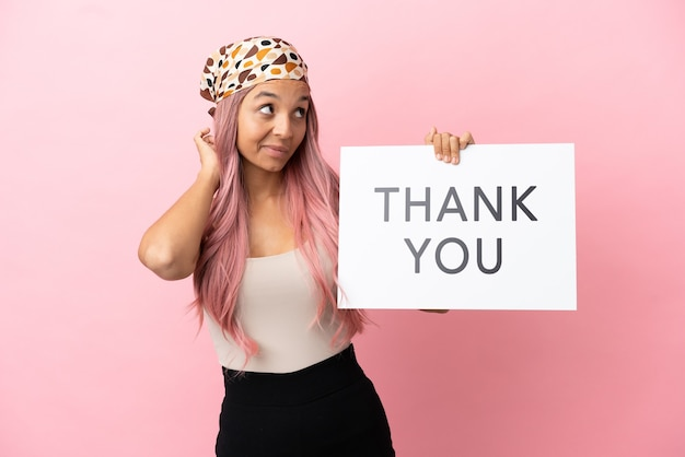 Young mixed race woman with pink hair isolated on pink background holding a placard with text thank you and thinking