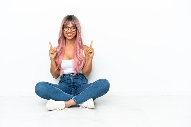 좋은 아이디어를 가리키는 흰색 배경에 고립 된 바닥에 앉아 분홍색 머리를 가진 젊은 혼혈 여성