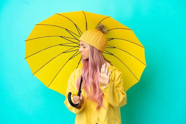 防雨コートと傘を持った若い混血の女性がジェスチャーを停止し、失望した
