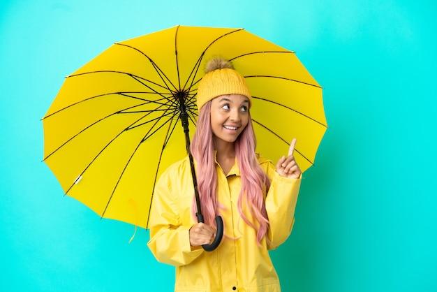 Молодая женщина смешанной расы с непромокаемым пальто и зонтиком указывает на отличную идею