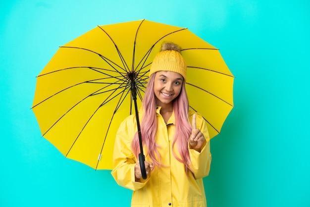 방수 코트와 우산을 보여주고 손가락을 드는 젊은 혼혈 여성