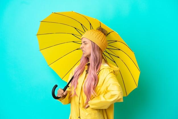 Молодая женщина смешанной расы с непромокаемым пальто и зонтиком страдает от боли в спине из-за того, что приложила усилие