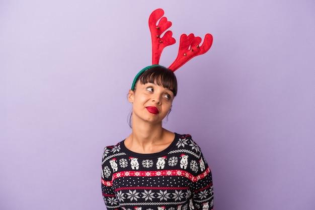 目標と目的を達成することを夢見ている紫色の背景に分離されたクリスマスを祝うトナカイの帽子を持つ若い混血の女性