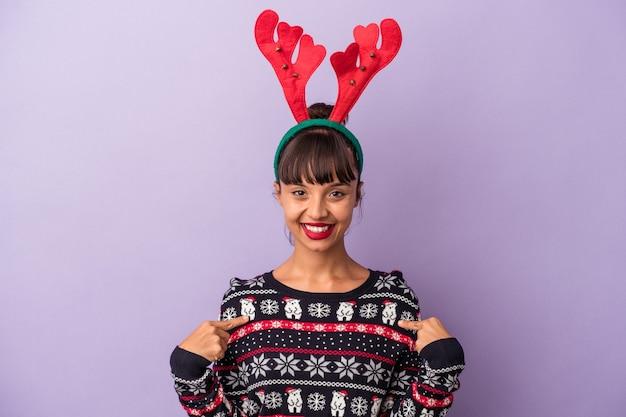 誇りと自信を持って、シャツのコピースペースを手で指している紫色の背景の人に分離されたクリスマスを祝うトナカイの帽子を持つ若い混血の女性