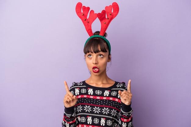 Молодая женщина смешанной расы в шляпе северного оленя празднует рождество, изолированную на фиолетовом фоне, указывая вверх с открытым ртом.