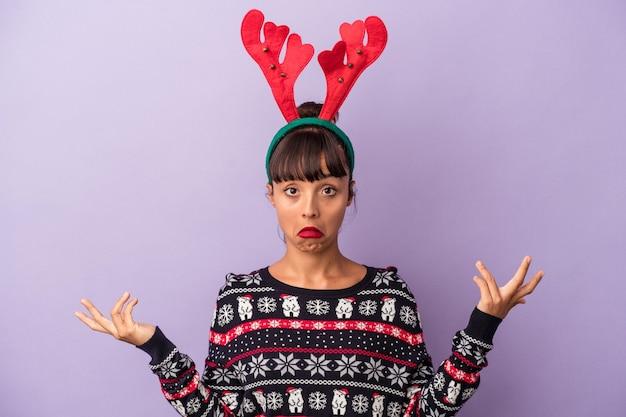 紫色の背景に分離されたクリスマスを祝うトナカイの帽子を持つ若い混血の女性は肩をすくめ、目を開けて混乱します。