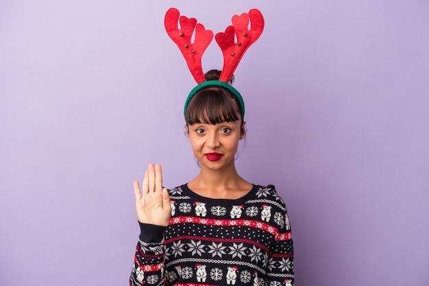 Молодая женщина смешанной расы в шляпе северного оленя, празднующая рождество, изолирована на фиолетовом фоне, стоя с протянутой рукой, показывая знак остановки, предотвращая вас.
