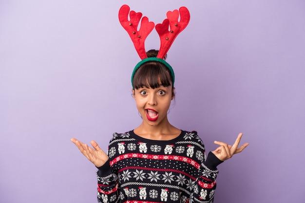 紫色の背景に分離されたクリスマスを祝うトナカイの帽子を持つ若い混血の女性は驚いてショックを受けました。